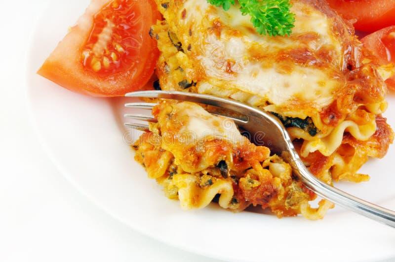 Lasagne und Tomaten mit Gabel lizenzfreies stockfoto