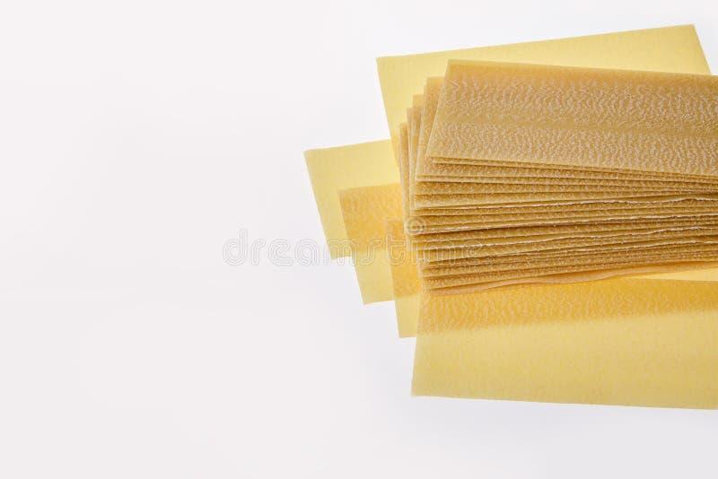 Lasagneblätter stapeln auf weißem Hintergrund stockbilder