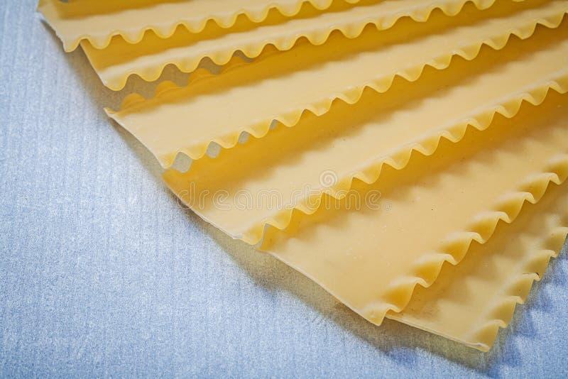 Lasagnepasta på blått bakgrundsmat och drinkbegrepp arkivfoto