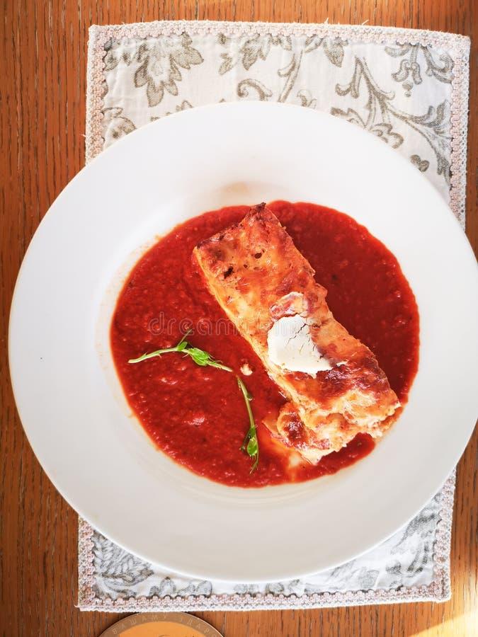 Lasanhas no molho de tomate Lasanhas italianas deliciosas saborosos do prato com molho e queijo creme de tomate com salat verde A foto de stock