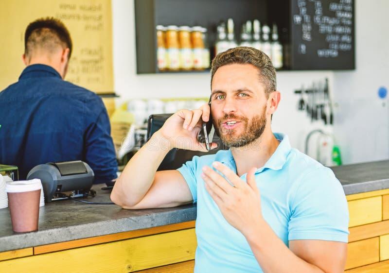 Lascia il raduno in caffè Fondo mobile di barista del caffè di conversazione dell'uomo Caffè della bevanda mentre aspettando Il c immagine stock
