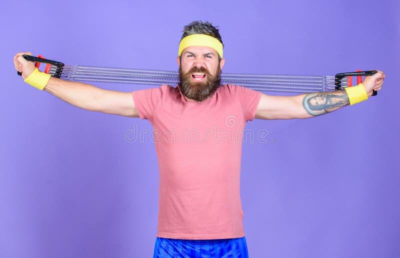 Lascia le armi di allungamento Atleta che allunga con l'estensore Atleta barbuto dell'uomo che si esercita con l'attrezzatura del immagini stock libere da diritti