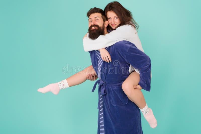 Lascia pantofolaio e si divertono Accoppi in accappatoi divertendosi il fondo del turchese Si divertono sempre insieme fotografia stock