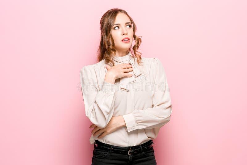 Lascilo pensare Donna pensierosa dubbiosa con l'espressione premurosa che opera scelta contro il fondo rosa fotografia stock libera da diritti