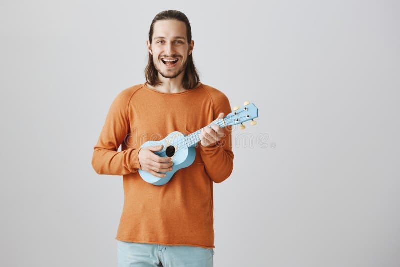 Lascimi cantare dal mio cuore Ritratto del ragazzo romantico affascinante in maglione arancio che tira le corde, tenente ukulele immagine stock libera da diritti