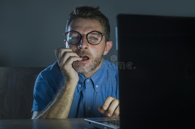 Lascivious aroused addict man in nerd glasses watching sex movie online late night at laptop computer looking pervert and. Young lascivious and aroused addict royalty free stock photography