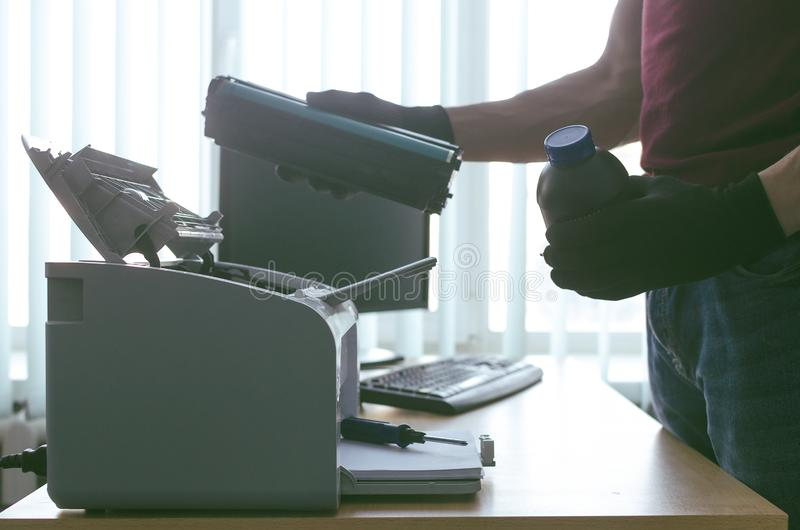 Laser printer cartridge repair. Laser cartridge toner refill concept. Office equipment maintenance concept royalty free stock image