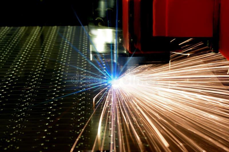 Laser-cutting av metallarket med sparks fotografering för bildbyråer