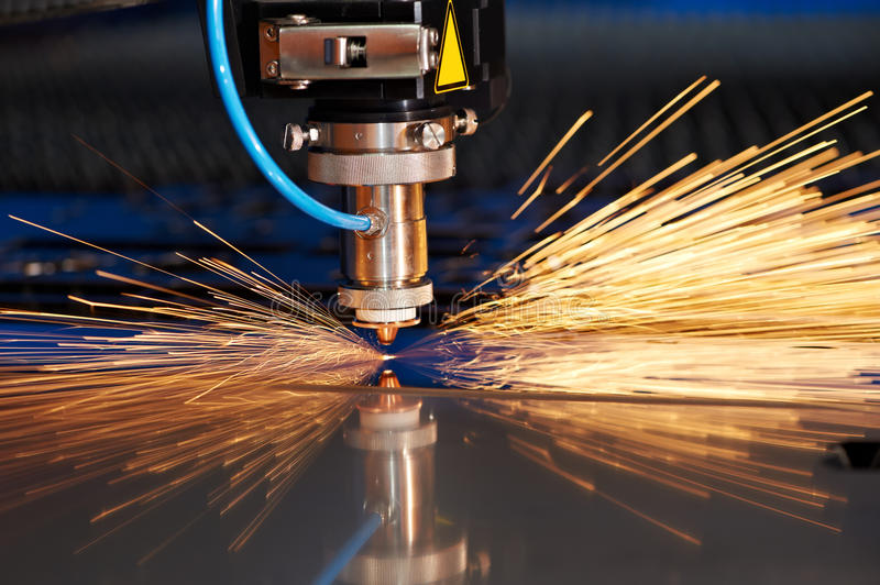 Laser cutting of metal sheet with sparks stock photography