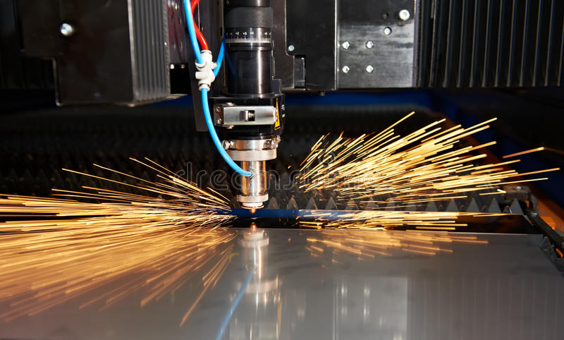 Laser cutting of metal sheet with sparks royalty free stock photography
