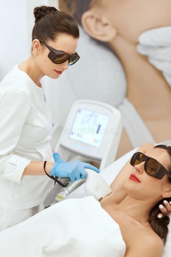Laser-epilation Kvinna på för laser för hårborttagning Underarm tillvägagångssätt arkivfoto