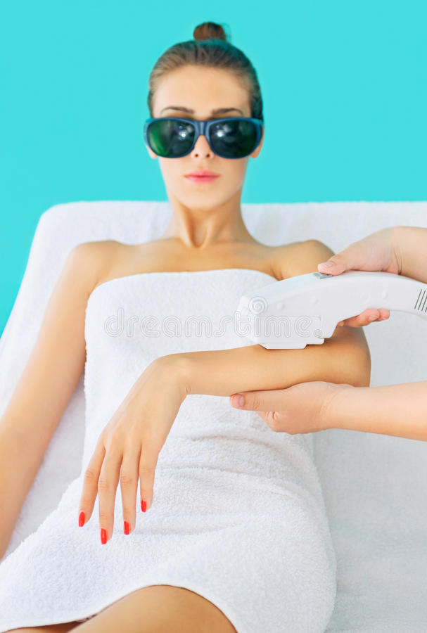 Laser epilation treatment. Electrolysis treatment in beuaty salon with beautician and young woma stock images