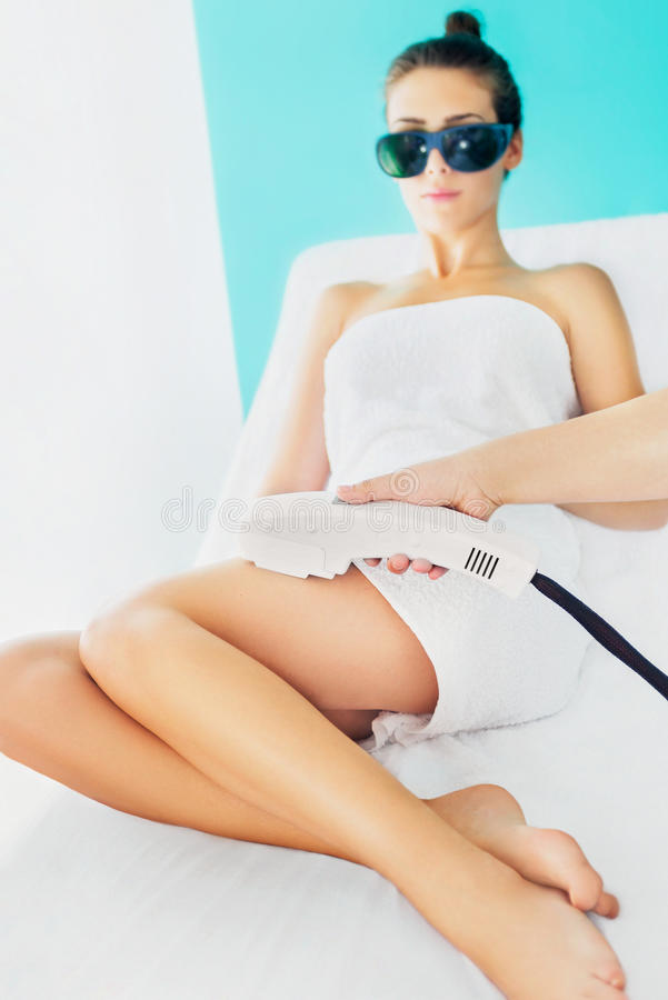 Laser epilation treatment. Electrolysis treatment in beuaty salon with beautician and young woman stock images