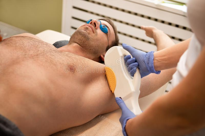 Laser-epilationbehandling på mans armhåla royaltyfri bild