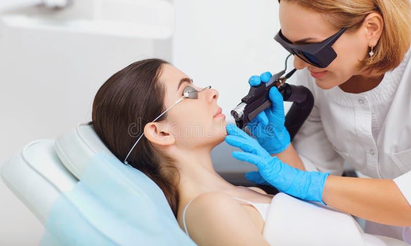 Laser-hårborttagning på framsidan av en ung kvinna i en cosmetology royaltyfri foto