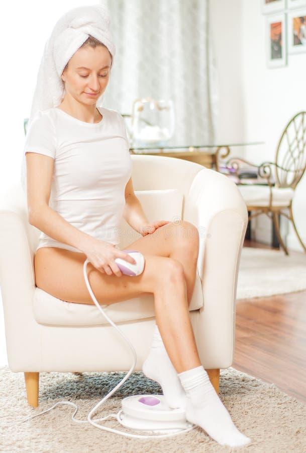 Laser-Haar-Abbau epilation Frau, die zu Hause Haar auf ihren Beinen entfernt lizenzfreie stockfotos