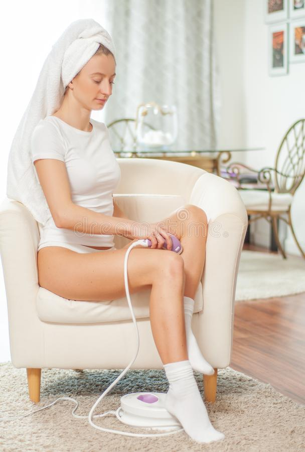 Laser-Haar-Abbau epilation Frau, die zu Hause Haar auf ihren Beinen entfernt stockfoto