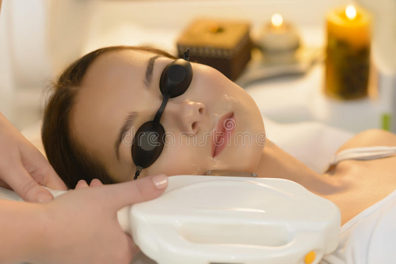 Laser Hair Removal. Beautiful woman getting laser hair removal at beauty salon royalty free stock photos