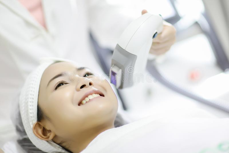 Laser Machine.Young woman receiving laser treatment.Skin Care.Young Woman Receiving Facial Beauty Treatment, Removing Pigmentation royalty free stock image