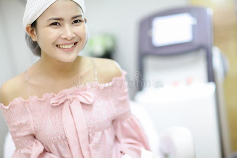 Laser-maskin Ung kvinna som mottar laser-behandling applicera genomskinlig fernissa för omsorgshud Behandling för skönhet för häl arkivfoton