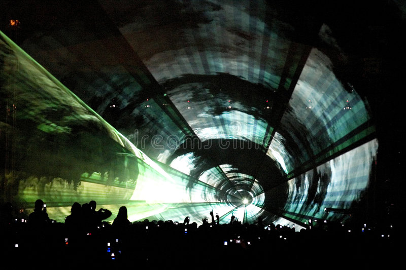 Laser party tunnel. A laser light show at a concert with party goers below and a kaleidescope of colours above. Very futuristic with silhouettes and special stock photo
