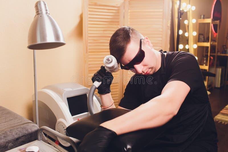 Laser profesional del retiro del tatuaje del Cosmetologist en salón imágenes de archivo libres de regalías
