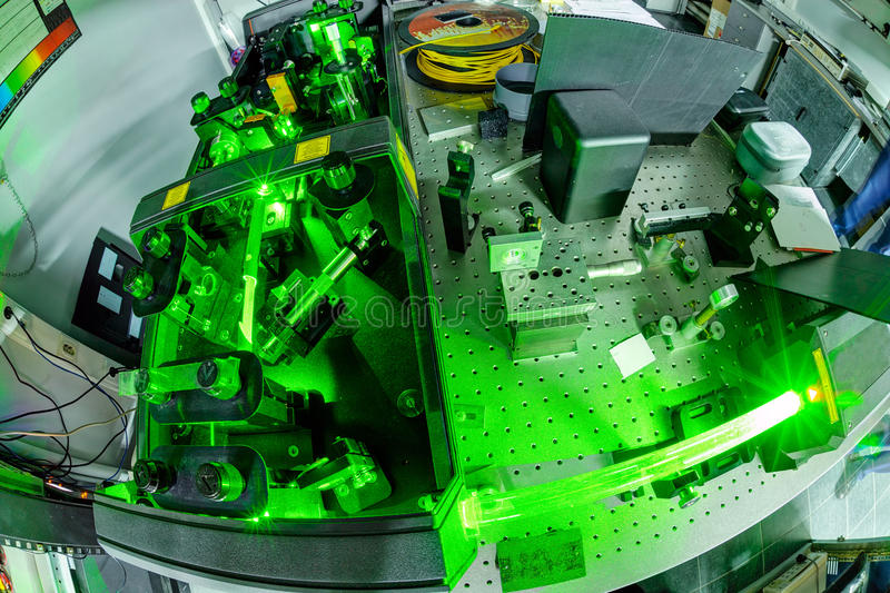 Laser in a quantum optics lab. Green laser on optical table in a quantum optics lab stock photo