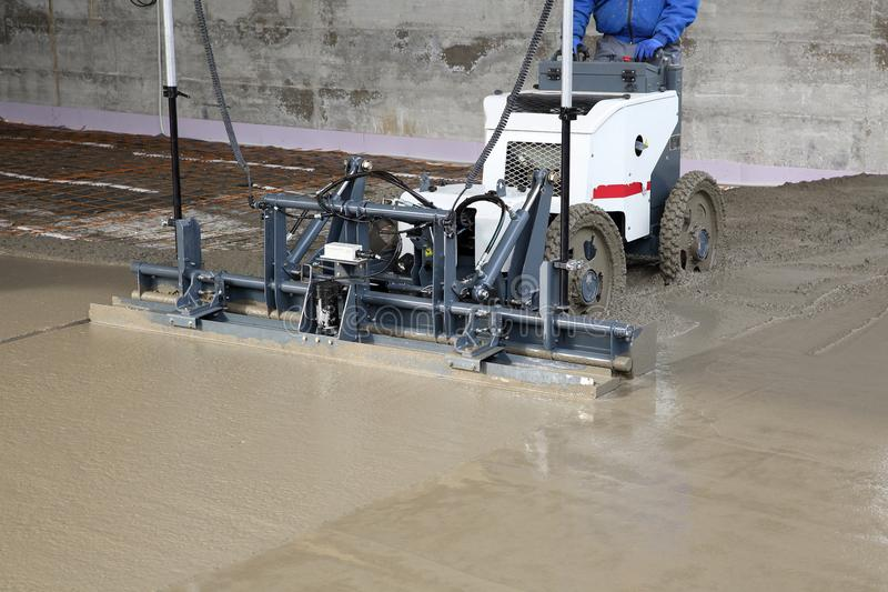 Laser screed machine leveling fresh poured concrete surface on a construction site royalty free stock photography