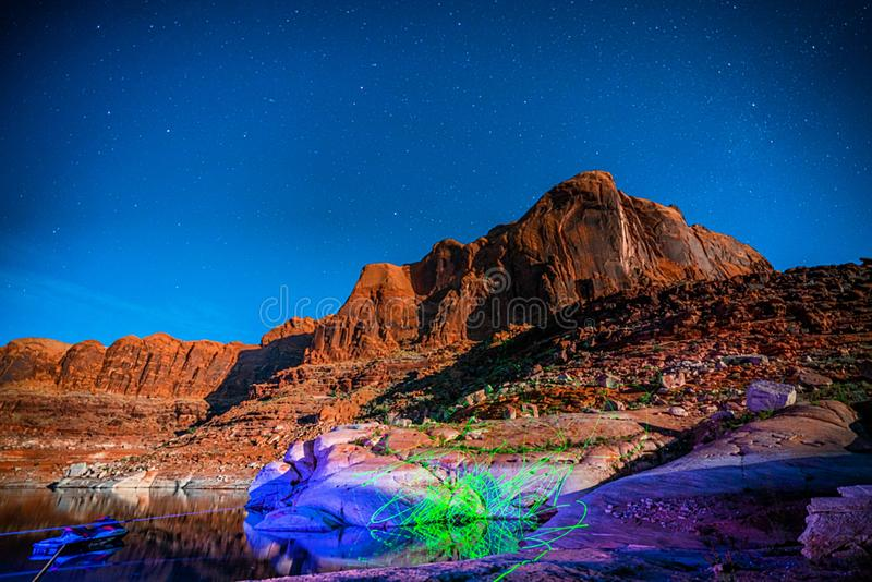 Laser show on Lake Powell Red Rock Mountains. Over house boat in the sandstone mountains of lake Powell area stock photo