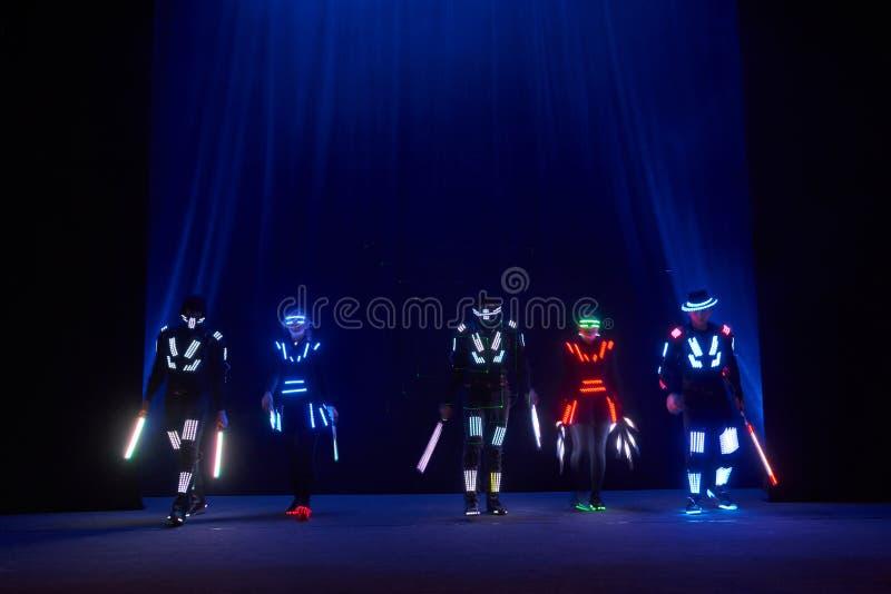 Laser-showkapacitet, dansare i ledde dräkter med den LEDDE lampan, mycket härlig nattklubbkapacitet, parti royaltyfri bild