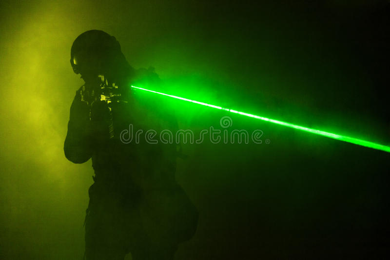 Laser sights. Studio shot of swat police operator with laser sights on rifle. Fire smoke screen green background. Laser rays beams diagonal stock photos