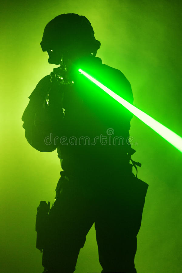Laser sights. Studio shot of swat police operator with laser sights on rifle. Fire smoke screen green background. Laser rays beams diagonal royalty free stock photography