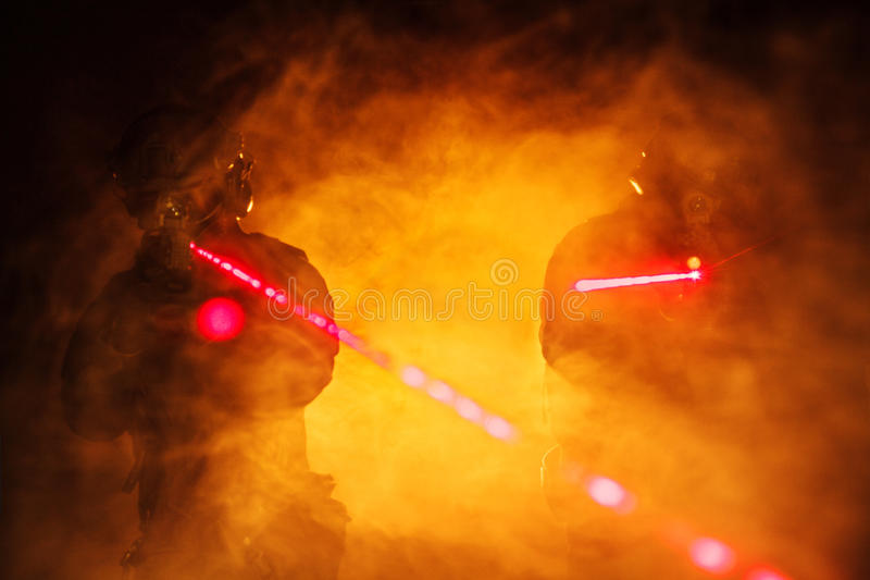 Laser sights in the smoke. Police officers SWAT in black uniform in the smoke with laser sights royalty free stock photos