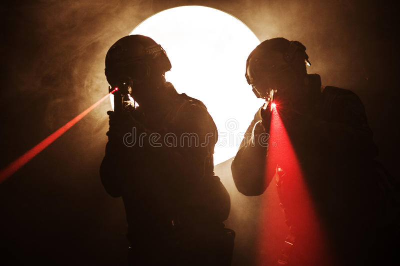 Laser sights. Spec ops police officers SWAT in the smoke and fire with laser sights stock image
