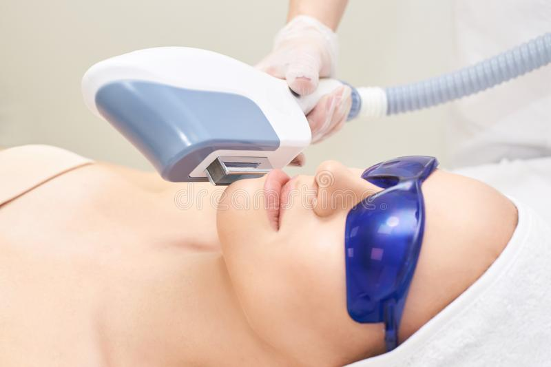 Laser unwanted hair cosmetology procedure. Beautiful young girl. Blue glasses. Face treatment. IPL machine.  royalty free stock photos