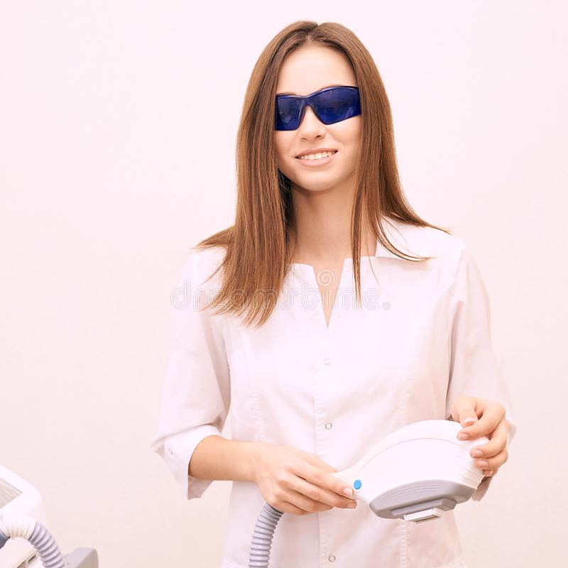 Laser unwanted hair cosmetology procedure. Beautiful young girl hold hand. Blue glasses. Removal treatment. IPL machine.  stock photography