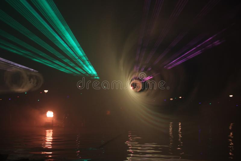 Laserstr?lar under en offentlig show i flera f?rger p? vattnet av Ringvaarten i Nieuwerkerk den aan h?lan IJssel royaltyfri foto