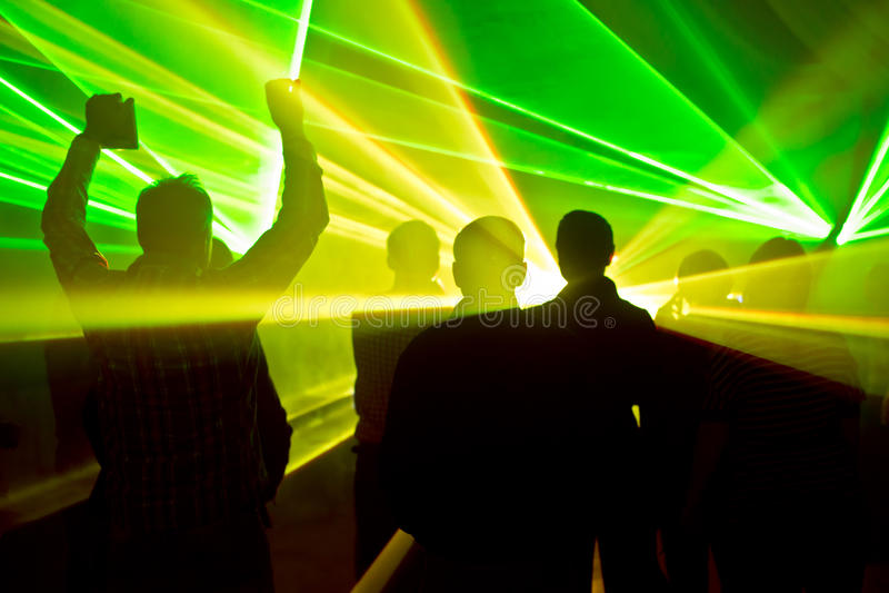 Lasery przy klubem nocnym i ludźmi sylwetek zdjęcia stock