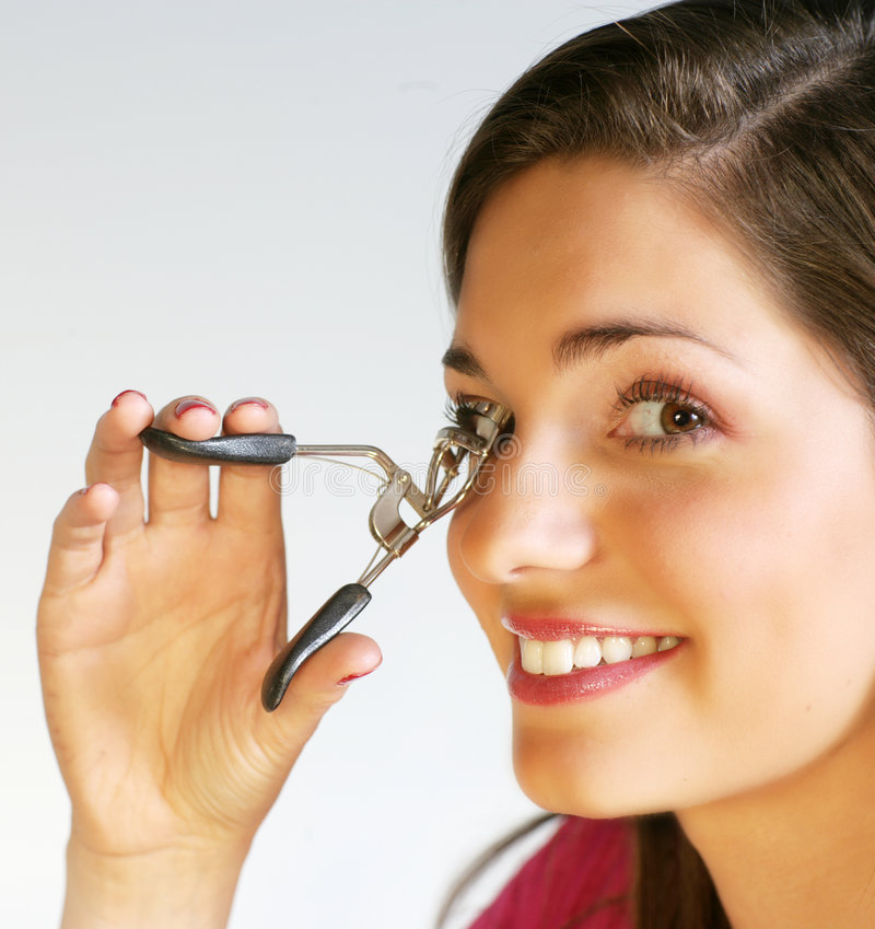 Lash curler. Close up picture of a pretty woman with a lash curler stock photos