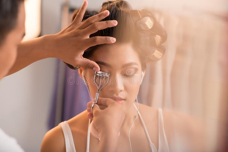 Lash curler. Make-up artist curling lashes of pretty model royalty free stock images