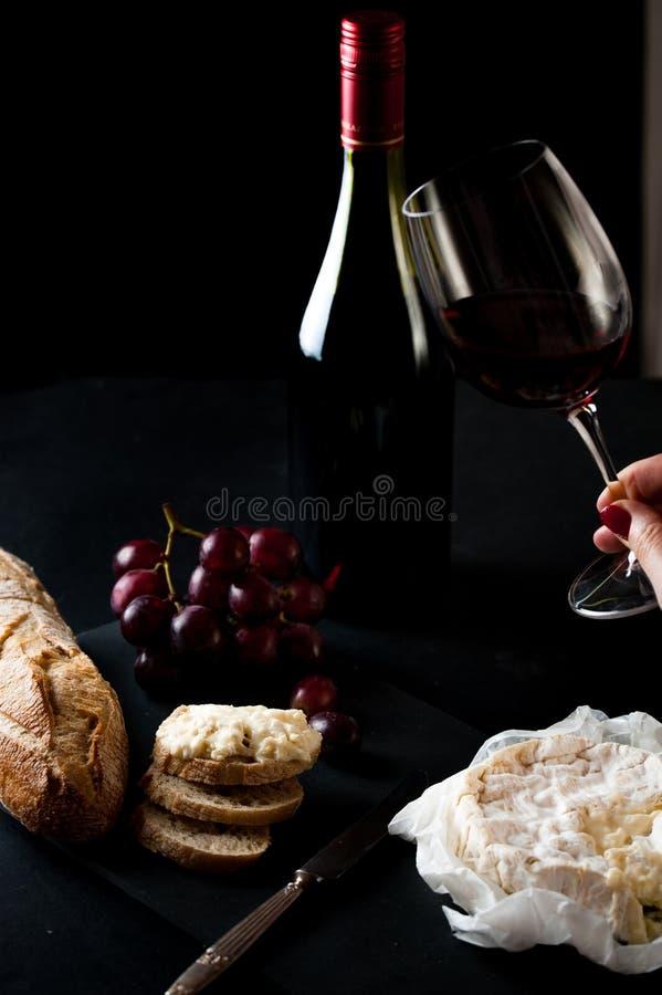 Lass czerwone wino z butelką, grono winogrona, kobiety wręcza umieszczać brie ser rustick kawałek chleb z antykwarskim nożem obrazy royalty free