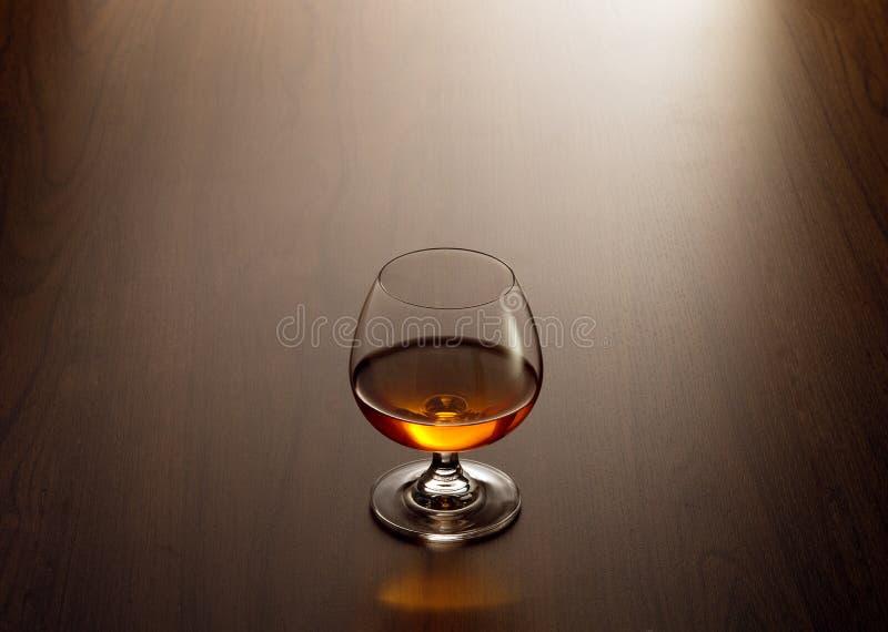 Lass van cognac op de bruine oppervlakte van de kleuren houten lijst stock foto's