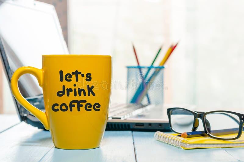 LASSEN Sie DIE US-GETRÄNK-KAFFEE-Aufschrift, die auf gelbe Schale mit Heißgetränk am Geschäftslokalarbeitsplatz geschrieben wird stockbild