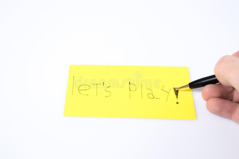 Lassen Sie ` s Spiel handwrite mit einem Stift und eine Hand auf einem gelben Papier stockfoto