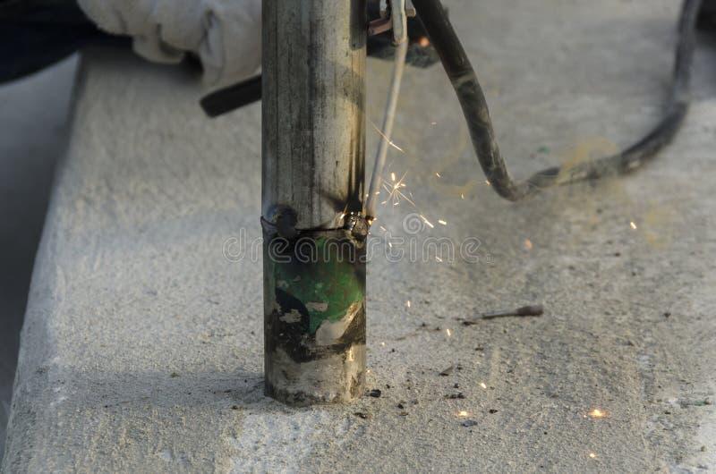 Lassen van een traliewerk tijdens de vernieuwing van een dak in de avond stock afbeeldingen