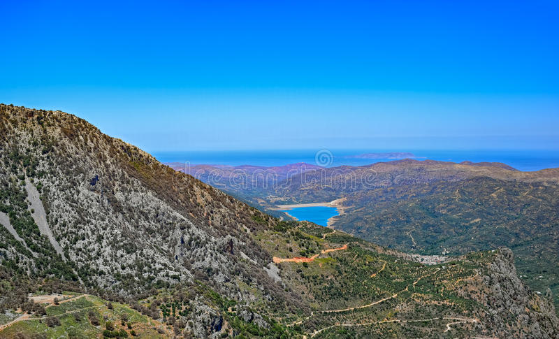 Lassithi Plateau on Crete island. Panoramic top view from mountain to Lassithi Plateau, famous landmark on Crete island royalty free stock images