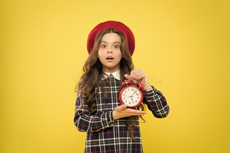 Last chance deadline. Anxious child worried about deadline on yellow background. Stressed little girl holding clock stock photography