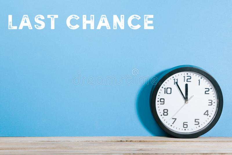 Last chance words on blue colored background with clock. Last Chance text on blue colored background wall with black clock on wooden desk royalty free stock image