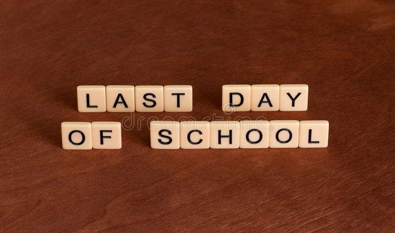 Last date of school. School`s Out concept. Ivory tiles with capital letters on mahogany board stock photos