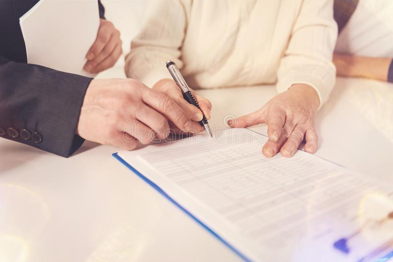 Pleasant elderly woman signing papers. Last formalities. Close up of elderly women signing papers while meeting with her insurance agent royalty free stock photo